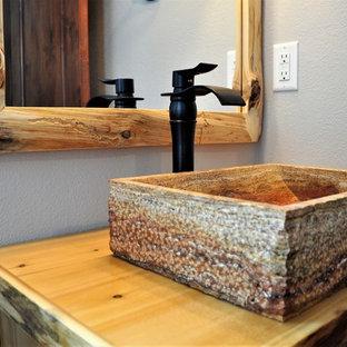 デンバーの中サイズのラスティックスタイルのおしゃれなトイレ・洗面所 (ヴィンテージ仕上げキャビネット、一体型トイレ、磁器タイルの床、ベッセル式洗面器、木製洗面台、白い床) の写真