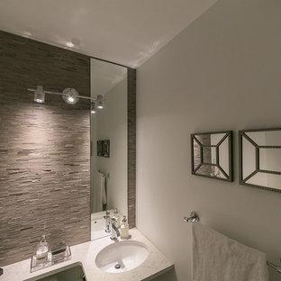 Неиссякаемый источник вдохновения для домашнего уюта: маленький туалет в стиле модернизм с врезной раковиной, столешницей из искусственного кварца, унитазом-моноблоком, белыми стенами, серой плиткой и удлиненной плиткой