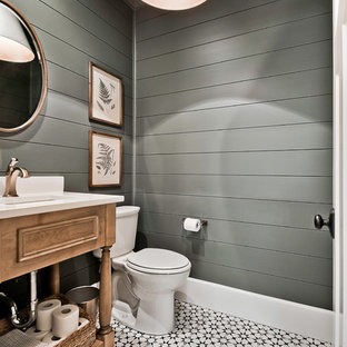 Photo of a large farmhouse cloakroom in Other with freestanding cabinets, a two-piece toilet, a submerged sink, engineered stone worktops, medium wood cabinets, grey walls and multi-coloured floors.