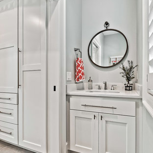 Example of a small arts and crafts ceramic floor powder room design in Other with raised-panel cabinets, white cabinets, a two-piece toilet, an undermount sink, engineered quartz countertops and white countertops