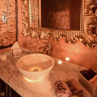 Photo of a classic cloakroom in Detroit with a vessel sink, dark wood cabinets, marble worktops, a one-piece toilet, multi-coloured tiles, porcelain tiles, pink walls and porcelain flooring.