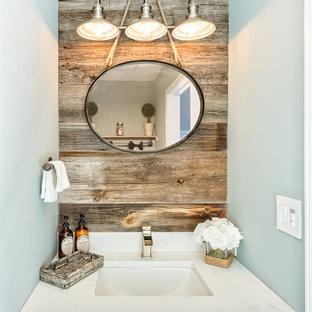 シカゴの小さいトランジショナルスタイルのおしゃれなトイレ・洗面所 (家具調キャビネット、濃色木目調キャビネット、茶色いタイル、青い壁、アンダーカウンター洗面器、分離型トイレ、濃色無垢フローリング、クオーツストーンの洗面台、茶色い床、白い洗面カウンター、造り付け洗面台、板張り壁) の写真