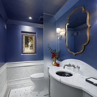 Inspiration for a timeless white tile and marble tile marble floor and white floor powder room remodel in DC Metro with furniture-like cabinets, gray cabinets, blue walls, an undermount sink, marble countertops and white countertops