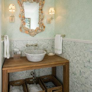 Свежая идея для дизайна: туалет в морском стиле с зеленой плиткой, серой плиткой, зелеными стенами, настольной раковиной, столешницей из дерева, открытыми фасадами, фасадами цвета дерева среднего тона, плиткой мозаикой и коричневой столешницей - отличное фото интерьера