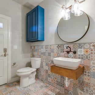 Пример оригинального дизайна: туалет среднего размера в стиле фьюжн с фасадами с филенкой типа жалюзи, светлыми деревянными фасадами, раздельным унитазом, разноцветной плиткой, керамической плиткой, серыми стенами, полом из керамической плитки, настольной раковиной, столешницей из дерева и разноцветным полом