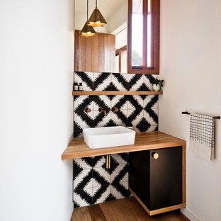Esempio di un bagno di servizio design con lavabo a bacinella, ante nere, top in legno, piastrelle di cemento, pareti bianche, pavimento in legno massello medio, pistrelle in bianco e nero e top marrone