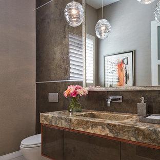 Идея дизайна: туалет в современном стиле с плоскими фасадами, коричневыми фасадами, инсталляцией, коричневой плиткой, коричневыми стенами, монолитной раковиной, коричневым полом и разноцветной столешницей