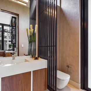 Diseño de aseo actual, grande, con armarios con paneles lisos, puertas de armario de madera oscura, sanitario de pared, paredes marrones, suelo de mármol, lavabo integrado, encimera de piedra caliza, encimeras beige y suelo beige