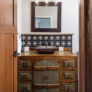 Réalisation d'un WC et toilettes champêtre avec meuble-lavabo encastré, un placard en trompe-l'oeil, des portes de placard marrons, un carrelage beige, un carrelage noir, un carrelage bleu, un mur blanc, une vasque, un plan de toilette en bois, un sol multicolore et un plan de toilette marron.