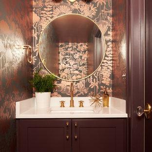 Cette photo montre un petit WC et toilettes chic avec un placard à porte shaker, des portes de placard marrons, un mur multicolore, un lavabo encastré, un plan de toilette en surface solide et un plan de toilette blanc.