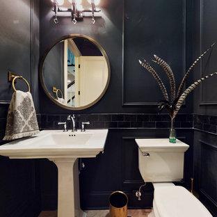 Inredning av ett klassiskt litet toalett, med en toalettstol med separat cisternkåpa, svart kakel, kakelplattor, svarta väggar, klinkergolv i porslin, ett piedestal handfat och flerfärgat golv