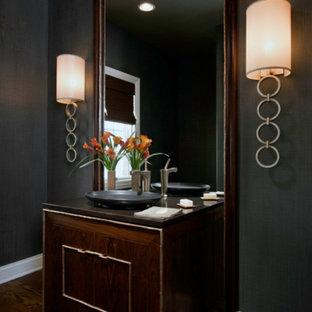 Réalisation d'un WC et toilettes design de taille moyenne avec un placard avec porte à panneau encastré, des portes de placard en bois sombre, un mur noir, un sol en bois foncé, une vasque, un plan de toilette en bois et un sol marron.