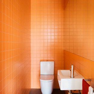 На фото: маленький туалет в современном стиле с подвесной раковиной, оранжевой плиткой, керамической плиткой, оранжевыми стенами, полом из керамогранита и раздельным унитазом с