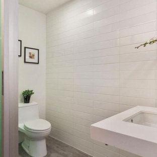 Example of a mid-sized trendy white tile and porcelain tile concrete floor powder room design in Boston with white walls, quartz countertops, a one-piece toilet and an undermount sink