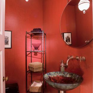 На фото: маленький туалет в стиле модернизм с подвесной раковиной, унитазом-моноблоком, красными стенами и стеклянной столешницей с