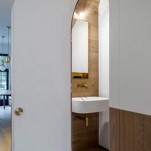 Modelo de aseo clásico renovado con paredes multicolor, suelo de madera clara, lavabo suspendido y suelo marrón