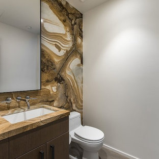 Inspiration for a medium sized contemporary cloakroom in Las Vegas with flat-panel cabinets, dark wood cabinets, a one-piece toilet, brown tiles, multi-coloured tiles, stone slabs, grey walls, a submerged sink, granite worktops and beige worktops.
