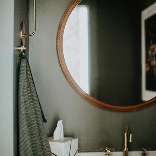 Modelo de aseo nórdico con armarios con paneles lisos, paredes verdes y encimera de cuarzo compacto