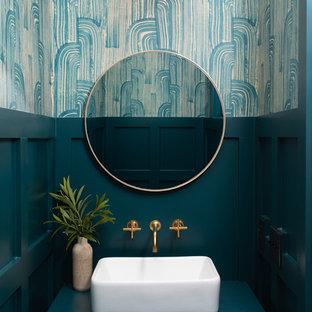 他の地域のビーチスタイルのおしゃれなトイレ・洗面所 (フラットパネル扉のキャビネット、緑のキャビネット、緑の壁、ベッセル式洗面器、グリーンの洗面カウンター) の写真
