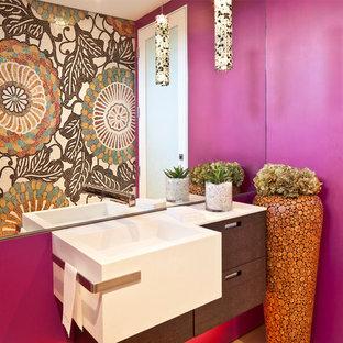 Bild på ett funkis vit vitt toalett, med ett väggmonterat handfat, släta luckor, skåp i mörkt trä och rosa väggar