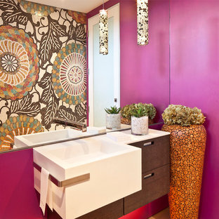 This is an example of a contemporary cloakroom in Los Angeles with a wall-mounted sink, flat-panel cabinets, dark wood cabinets, pink walls and white worktops.
