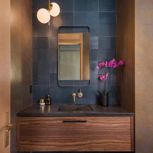 На фото: туалет в современном стиле с подвесной тумбой, плоскими фасадами, фасадами цвета дерева среднего тона, керамической плиткой, монолитной раковиной, серым полом, черной столешницей, обоями на стенах, черной плиткой и коричневыми стенами