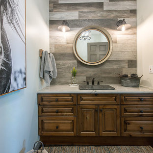 This is an example of a medium sized rustic cloakroom in Calgary with raised-panel cabinets, distressed cabinets, a two-piece toilet, multi-coloured tiles, ceramic tiles, white walls, medium hardwood flooring, a built-in sink, quartz worktops, grey floors and white worktops.