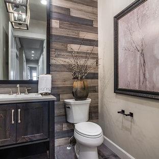 Modelo de aseo campestre con armarios estilo shaker, puertas de armario de madera en tonos medios, sanitario de dos piezas, paredes grises, lavabo encastrado, suelo gris y encimeras grises