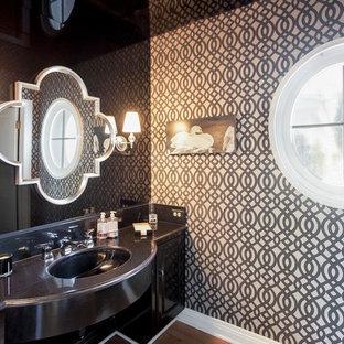 Cette image montre un WC et toilettes traditionnel avec un lavabo encastré, des portes de placard noires, un carrelage noir, des plaques de verre et un plan de toilette noir.