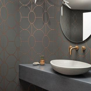 Modern inredning av ett grå grått toalett, med grå väggar, mellanmörkt trägolv, ett fristående handfat och bänkskiva i betong
