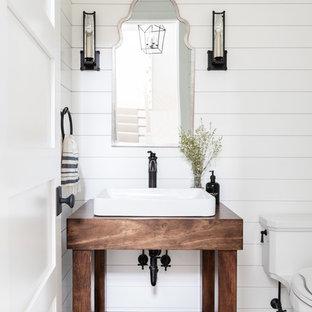 Kleine Landhaus Gästetoilette mit offenen Schränken, dunklen Holzschränken, Wandtoilette mit Spülkasten, weißer Wandfarbe, hellem Holzboden, Aufsatzwaschbecken, Waschtisch aus Holz, beigem Boden und brauner Waschtischplatte in Chicago