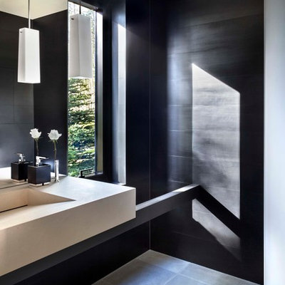 Trendy black tile powder room photo in Denver with an integrated sink