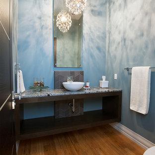 Imagen de aseo moderno, de tamaño medio, con lavabo sobreencimera, puertas de armario de madera en tonos medios, encimera de mármol, baldosas y/o azulejos de porcelana, paredes azules, suelo de bambú y armarios abiertos