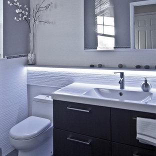 ニューヨークの小さいモダンスタイルのおしゃれなトイレ・洗面所 (一体型シンク、フラットパネル扉のキャビネット、濃色木目調キャビネット、一体型トイレ、白いタイル、セラミックタイル、グレーの壁、磁器タイルの床) の写真