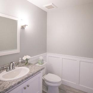 他の地域のトラディショナルスタイルのおしゃれなトイレ・洗面所 (フラットパネル扉のキャビネット、白いキャビネット、ラミネートカウンター、グレーのタイル、グレーの壁、磁器タイルの床、オーバーカウンターシンク、ベージュの床) の写真