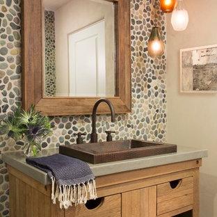Idee per un bagno di servizio bohémian con lavabo da incasso, nessun'anta, top in cemento e pareti beige