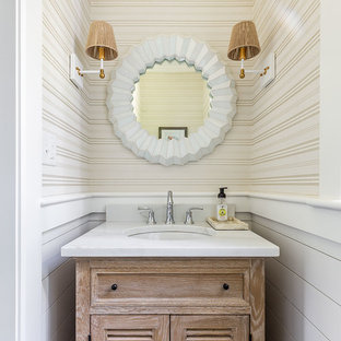 Small beach style powder room in Boston with louvered cabinets, light wood cabinets, beige walls, an undermount sink and white benchtops.