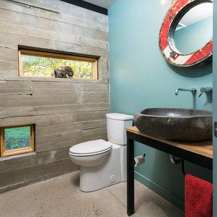 Kleine Industrial Gästetoilette mit Wandtoilette mit Spülkasten, blauer Wandfarbe, Betonboden, Aufsatzwaschbecken, schwarzen Schränken, Waschtisch aus Holz, beigem Boden und brauner Waschtischplatte in Philadelphia