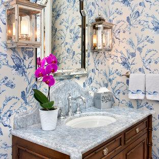 Idee per un piccolo bagno di servizio tropicale con consolle stile comò, ante in legno scuro, pareti multicolore, lavabo sottopiano, top in marmo e top grigio