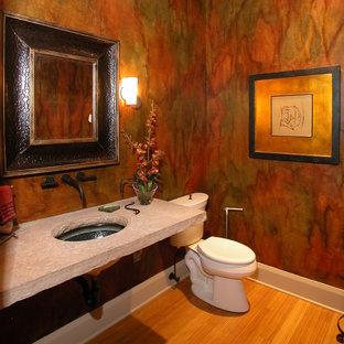 Diseño de aseo actual, de tamaño medio, con sanitario de dos piezas, parades naranjas, suelo de bambú, lavabo bajoencimera y encimera de piedra caliza