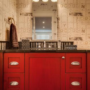 Aménagement d'un petit WC et toilettes classique avec un placard avec porte à panneau encastré, des portes de placard rouges, un carrelage noir, un mur multicolore, un lavabo encastré et un plan de toilette en granite.