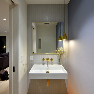 Идея дизайна: туалет среднего размера в стиле модернизм с инсталляцией, серой плиткой, керамической плиткой, серыми стенами, светлым паркетным полом, подвесной раковиной, столешницей из искусственного камня и бежевым полом