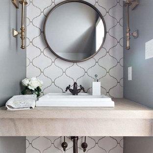 バーミングハムの小さいトランジショナルスタイルのおしゃれなトイレ・洗面所 (白いタイル、セメントタイル、オーバーカウンターシンク、ライムストーンの洗面台、茶色い床、ベージュのカウンター) の写真