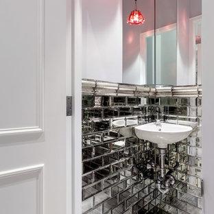Réalisation d'un petit WC et toilettes design avec des carreaux de miroir, un mur blanc, un sol en carrelage de porcelaine et un lavabo suspendu.