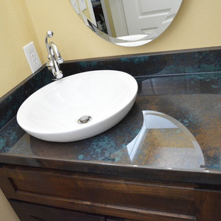 Inspiration pour un petit WC et toilettes urbain avec un placard avec porte à panneau encastré, des portes de placard en bois sombre, un mur jaune, une vasque, un plan de toilette en zinc et un plan de toilette multicolore.