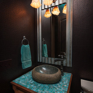 Стильный дизайн: маленький туалет в стиле фьюжн с настольной раковиной, фасадами с выступающей филенкой, фасадами цвета дерева среднего тона, столешницей из плитки, синей плиткой, стеклянной плиткой, коричневыми стенами и раздельным унитазом - последний тренд