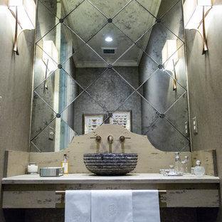 Стильный дизайн: большой туалет в стиле современная классика с настольной раковиной, искусственно-состаренными фасадами, столешницей из дерева, зеркальной плиткой и серой столешницей - последний тренд