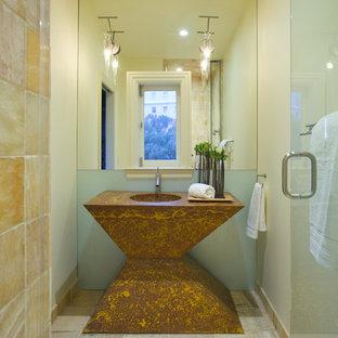 Пример оригинального дизайна: маленький туалет в современном стиле с плиткой из листового стекла, желтыми стенами и монолитной раковиной