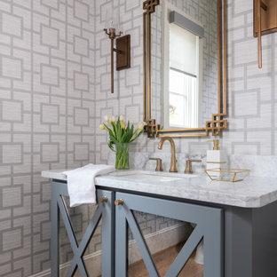 ヒューストンの中くらいのトランジショナルスタイルのおしゃれなトイレ・洗面所 (ガラス扉のキャビネット、グレーのキャビネット、グレーの壁、淡色無垢フローリング、アンダーカウンター洗面器、大理石の洗面台、茶色い床、白い洗面カウンター) の写真