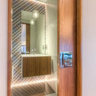 На фото: огромный туалет в стиле модернизм с монолитной раковиной, плоскими фасадами, столешницей из кварцита, унитазом-моноблоком, разноцветной плиткой, плиткой мозаикой, белыми стенами, полом из керамической плитки и фасадами цвета дерева среднего тона